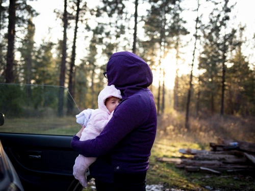 Woman dressed in purple carrying infant