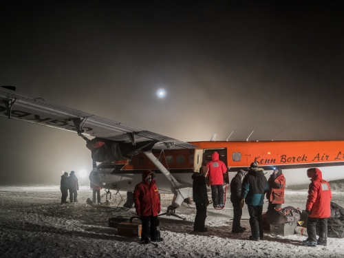 crew in orange parkas loading small plane at night