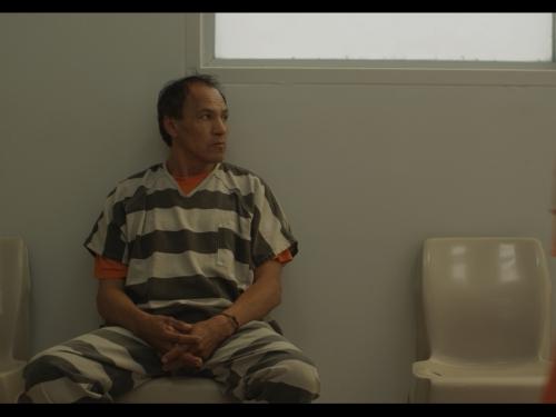 Still from film Mekko, showing man in jail cell