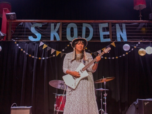 Woman performing on stage with guitar, SKODEN banner behind her
