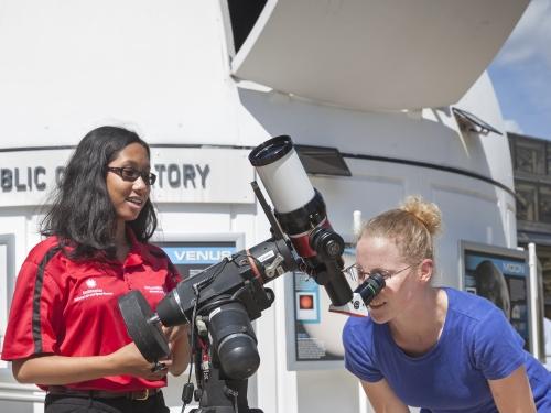 Two girls using telescope