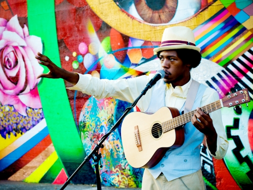 Musician in front of colorful mural