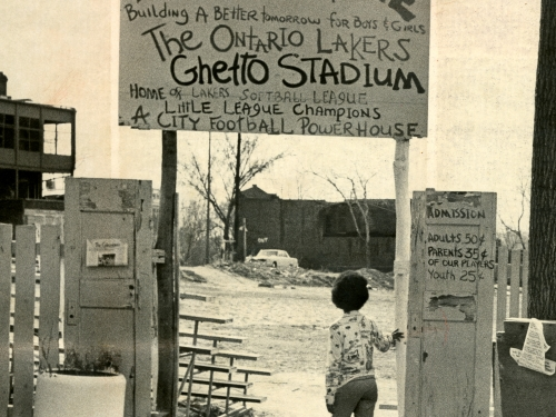 Child stands beneath welcome sign