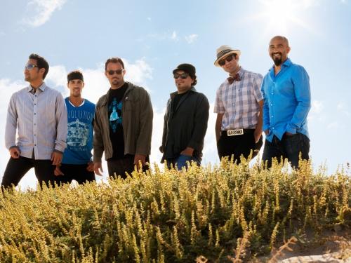 Ozomatli band standing in green field