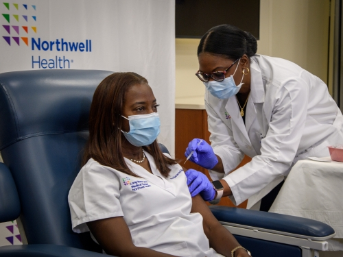Woman wearing mask receives vaccine shot from doctor