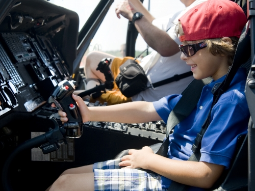 Child wearing red cap in airplane cockpit