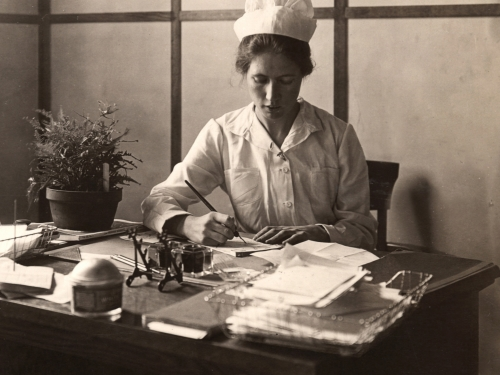 Nurse writes at desk
