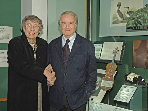 Two people shaking hands in front of a museum exhibit case