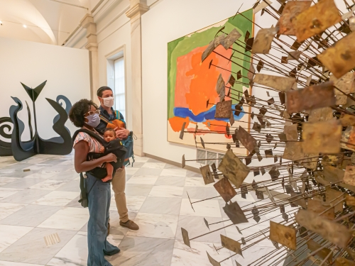 Two people carrying children look at sculpture in a museum