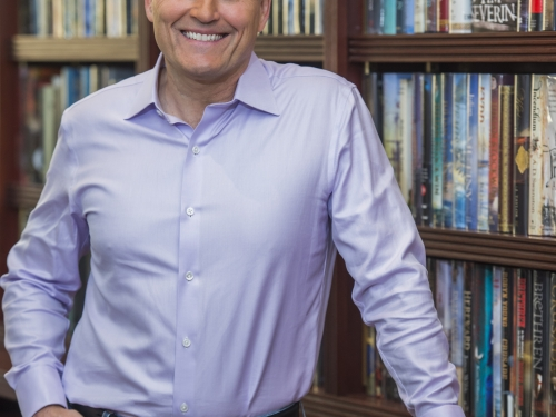 David Baldacci leans against bookcase