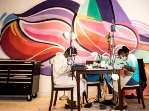 Two people working at a table in front of brightly painted mural