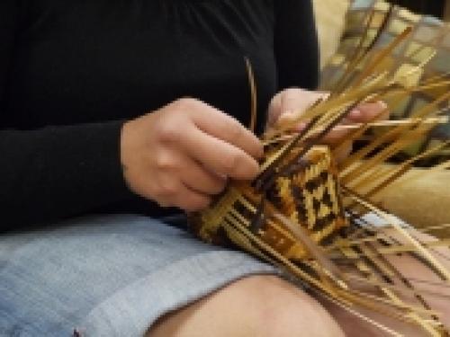 Closeup of person weaving a basket