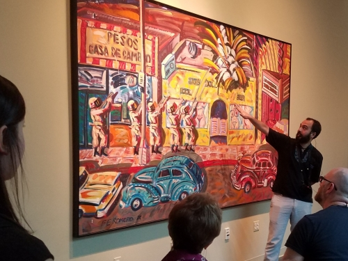 Docent explaining large colorful painting to onlookers