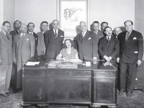 woman at a desk with group of men standing behind her.