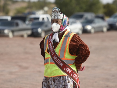 Woman wearing safety gear, headdress, and sash stands in a dirt field with cars in background.