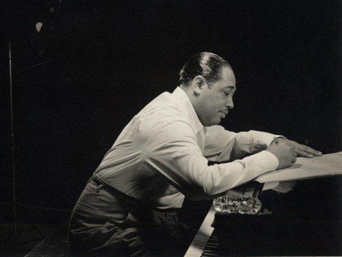 Duke Ellington in profile leaning over a piano
