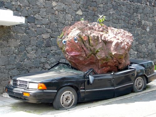 Car being squashed by sculpture that looks like crumpled paper bag