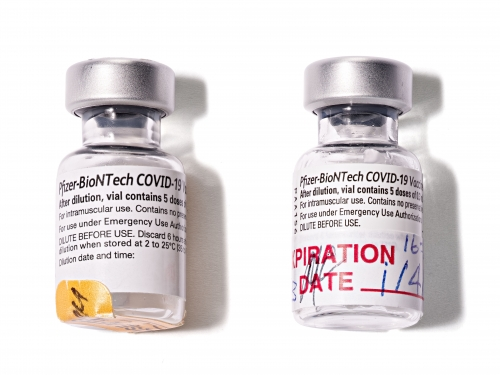 Two vials of covid-19 vaccine and vaccine card