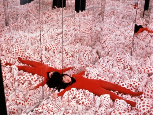 Woman lying amid red and white dots in mirrored room