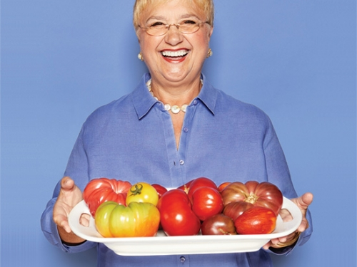 Smiling woman holding tray of fruit