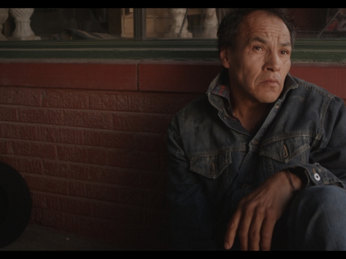 Still from film showing man sitting on a bench