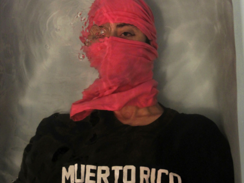 Portrait of man in red head scarf and black shirt saying Muerto Rico