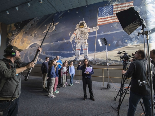 Group of children watch woman being filmed by cameramen in front of mural depicting space