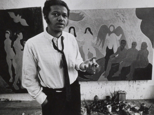 Man (Bob Thompson) standing in front of paintings