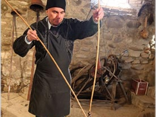 Man in ethnic dress demonstrating traditional wine-making