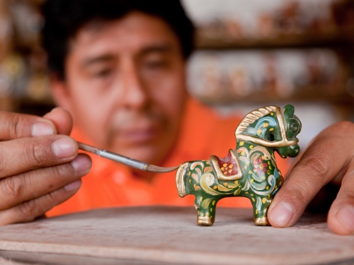 Artists painting a small horse figurine