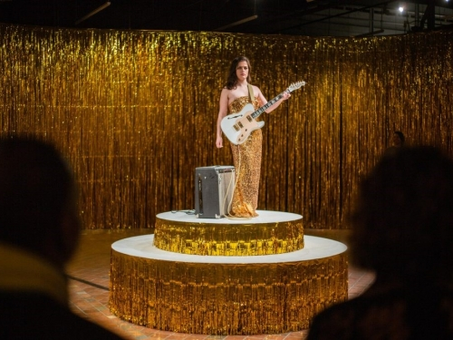 Woman in gold dress holding guitar on dais