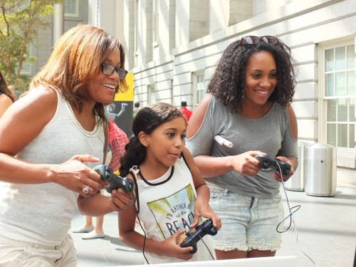 Two women and a girl with video game controllers