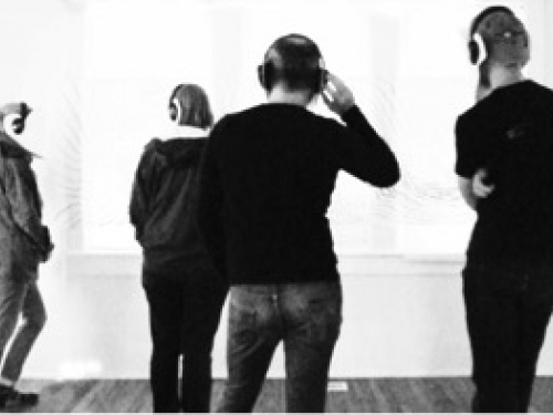 Black and white image of people listening