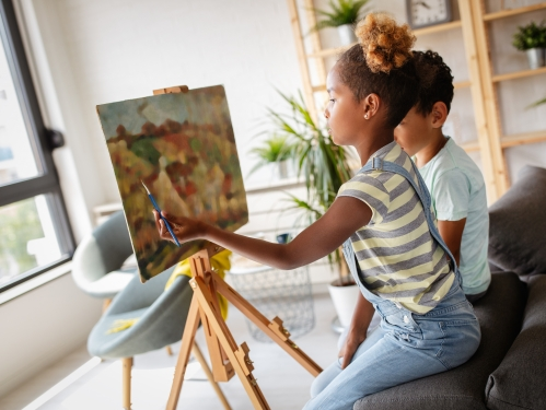 Young girls sits and paints at an easel in her home
