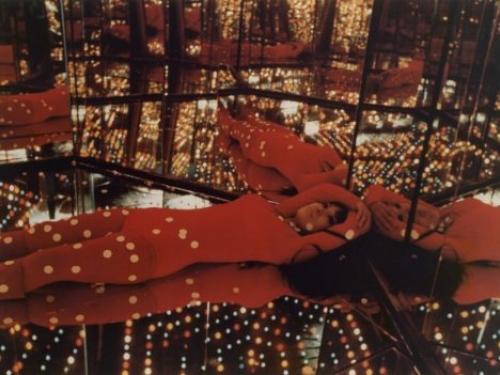 Woman lying on floor of mirrored room