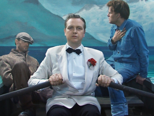 Cropped image of man in dinner jacket rowing a boat