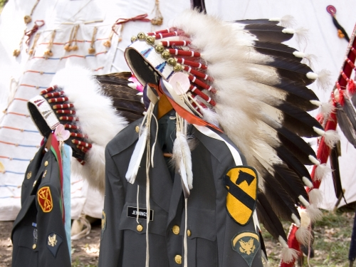 miltary uniforms draped with eagle feather bonnets