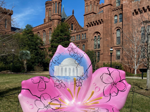 Sculpture shaped like cherry blossom sits in front of Smithsonian Castle