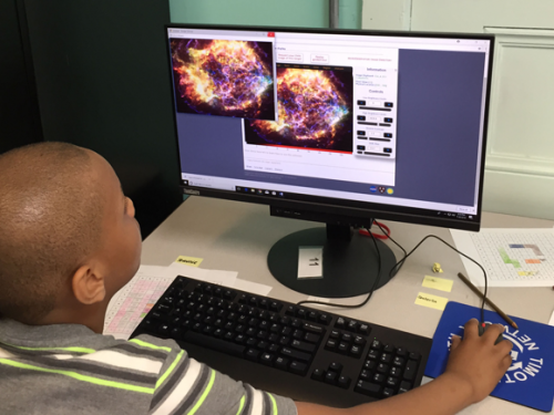 Child looks at a computer monitor