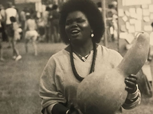 Woman singing and banging a gourd drum