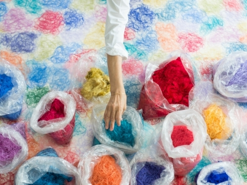 Bags of brightly colored thread seen from above