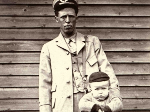 Photo of mail carrier with baby in a mailbag