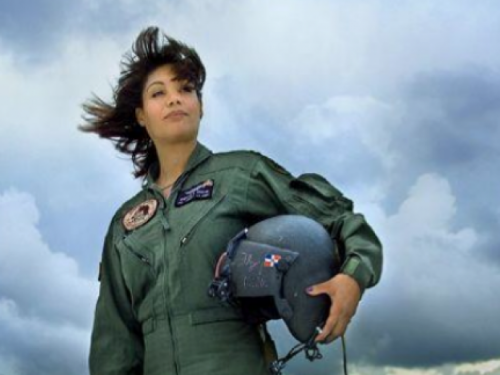 Marisol Chalas wearing her flight uniform and holding a helmet standing against a cloud-filled sky.