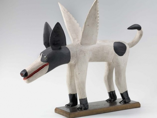 carved wooden dog with a black head, white body, and wings.
