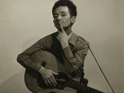 Woody Guthrie with a finger over his mouth as in thought while holding a guitar.