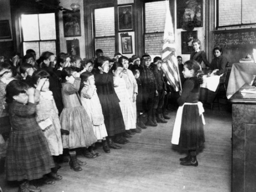 Black and white photograph of a classroom of elementary-age schoolchildren reciting a pledge to the U.S. flag.