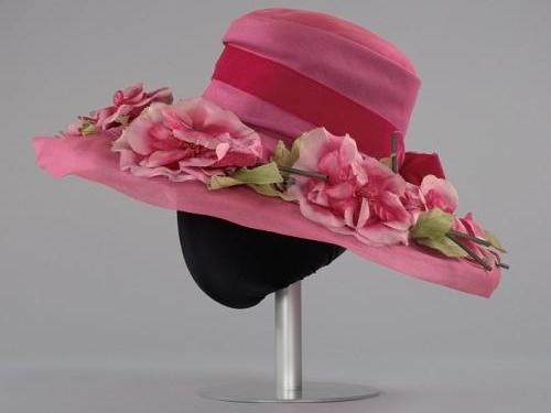 Pink hat adorned with pink flowers.