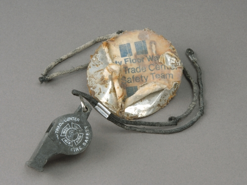 Whistle and badge, recovered during the September 11, 2001 recovery operation at Fresh Kills, Staten Island, New York.