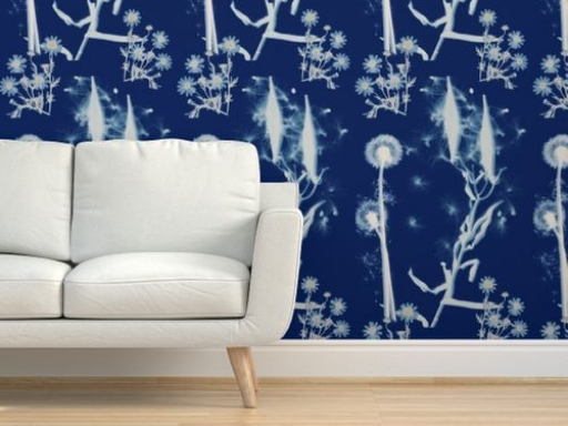 white modern sofa in front of royal blue wall paper with white dandelion silhouettes creating a repeating pattern