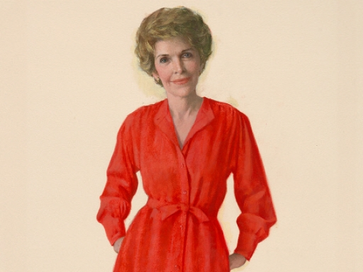 Nancy Reagan in a red dress with her hands in her pockets.